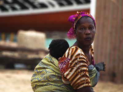 Una mujer con su bebe en la playa de Ngor