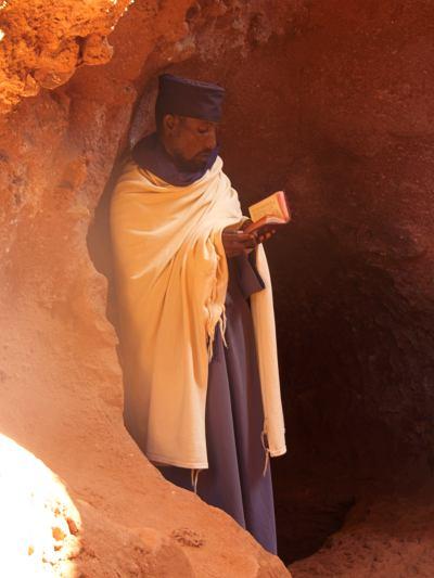 Un monje leyendo en una iglesia excavada
