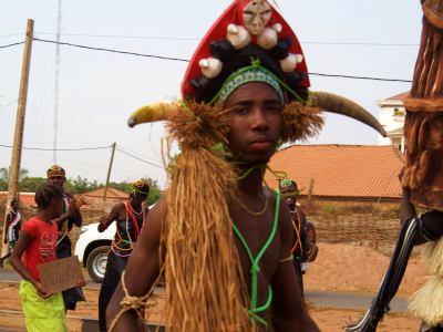 Un chico con máscaras de carnaval en Bissau