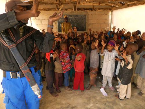 Un guardian dentro de la clase protege a los niños de Un profesor dando su clase en Shuawari nº5 con su machete