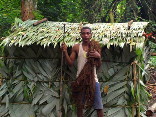 Un pigmeo delante de su cabaña