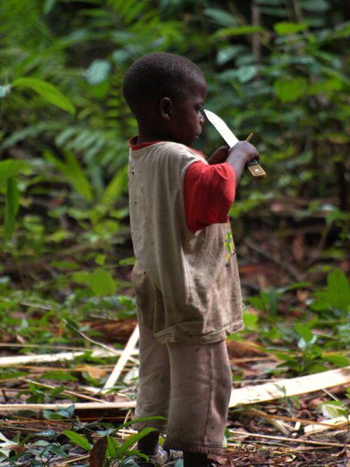 Un niño pigmeo jugando con un cuchillo