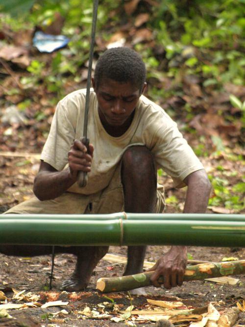 Un pigmeo trabaja artesanalmente en su poblado de Camarún