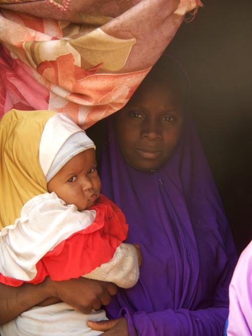 Una mujer en su casa con su hijo en Kano