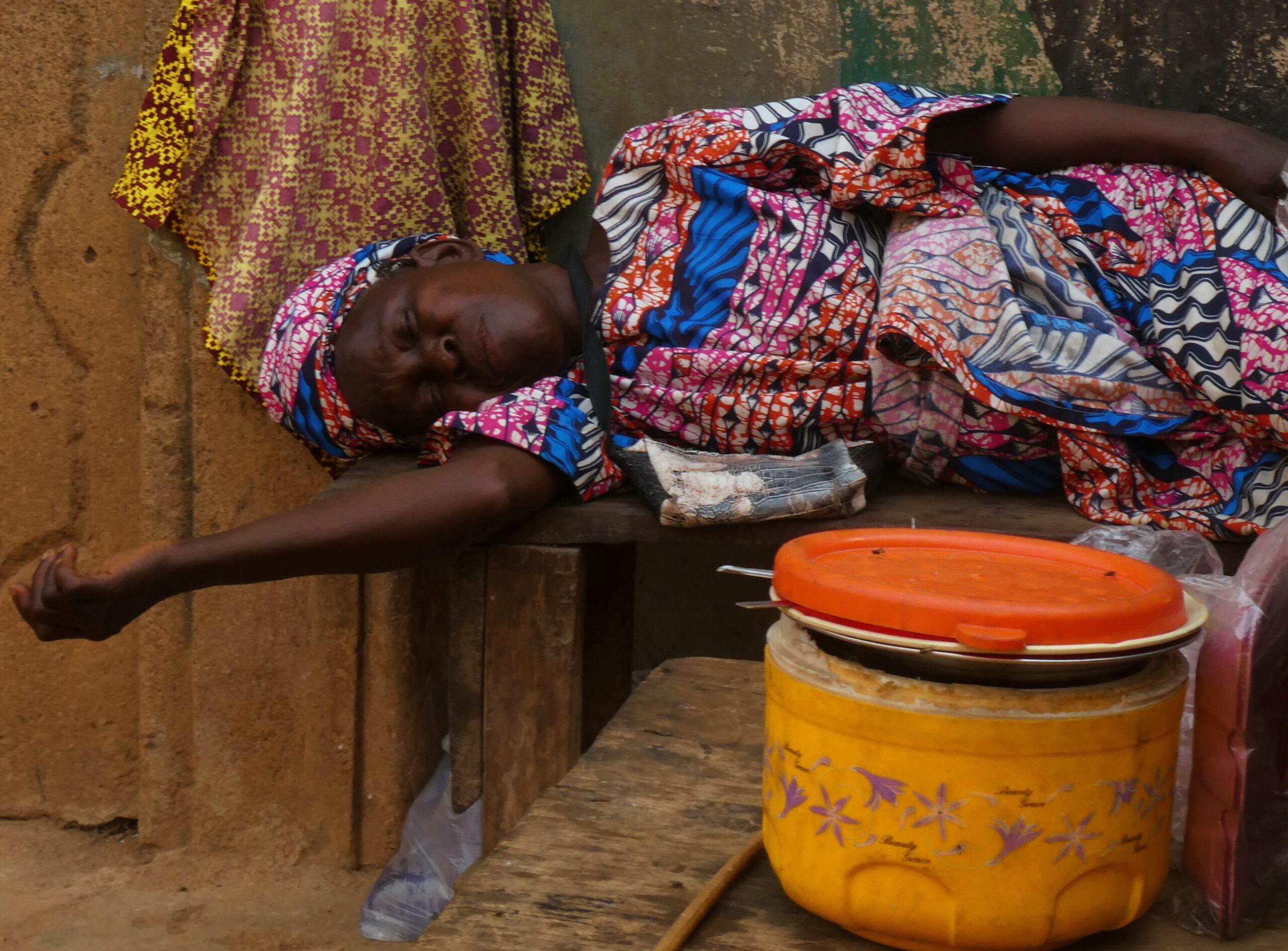 Una mujer durmiendo a la puerta de su casa en Nigeria
