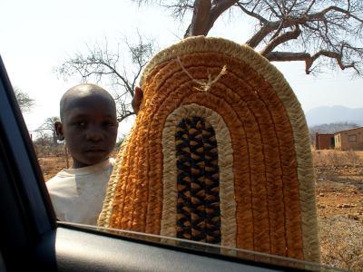 Un crio vendiendo artesania al paso de su poblado