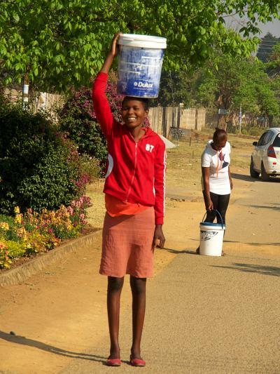 Dos mujeres cogen agua de un pozo limpio en Harare