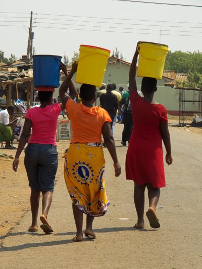 Tres mujeres se llevan agua del pozo de Oxfam en Harare