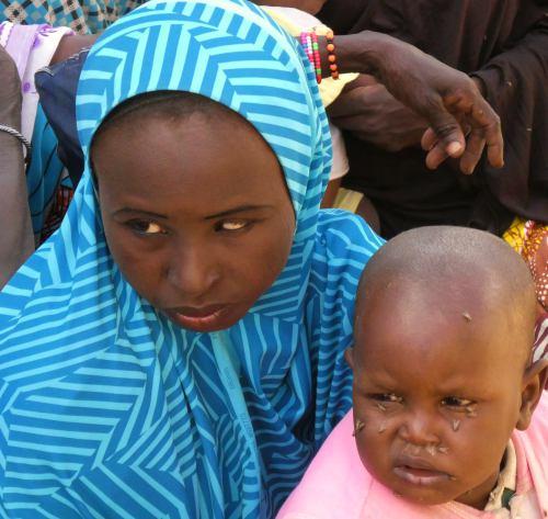 Una mujer con su niños lleno de moscas en Shuawari nº 5 Maiduguri